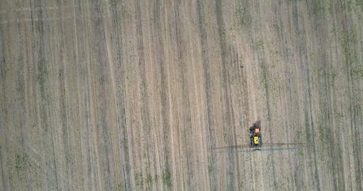 camera follows over tractor sprayer moving on field Live Action