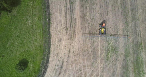 tractor sprayer moves on harvested field along forest Live Action