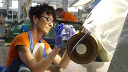 Glassworks. Glassware factory. Employee is grinding pattern Footage