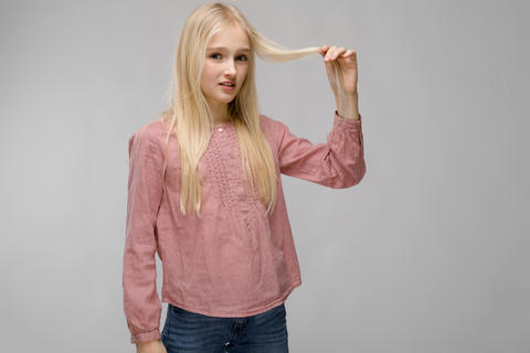 Portrait of attractive sweet adorable blonde teenager girl in pink blouse on Photo