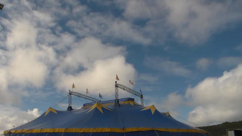 running white clouds in blue sky background over circus tent. Accelerated video. Footage