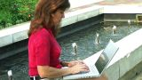 Female Typing By Fountain stock footage