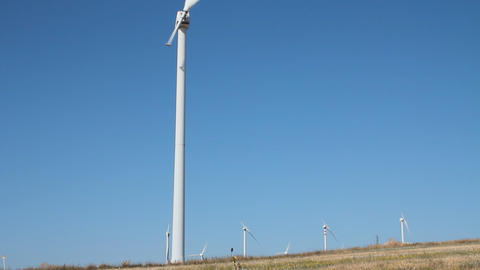 Single blade wind turbine in function and plants Stock Video Footage