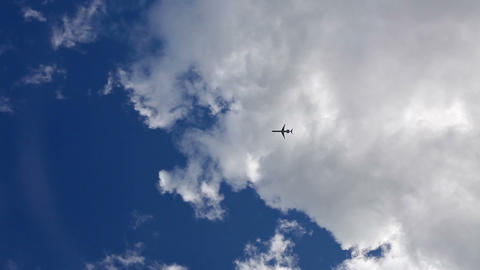 Aircraft silhouette flying in the blue cloudy sky Stock Video Footage