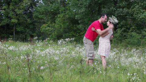 Husband brings flowers for his pregnant wife on the green meadows Footage