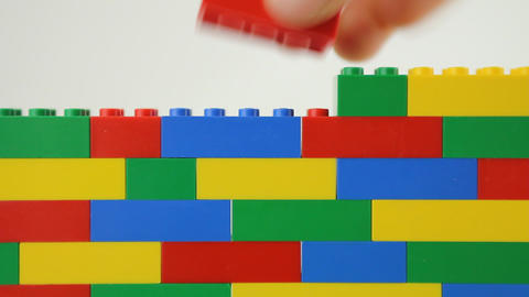 Hand adding blocks to lego wall Stock Video Footage