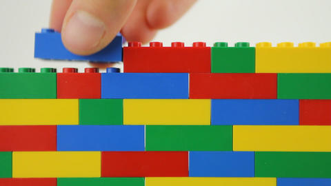 Hand adding blocks to lego wall Footage
