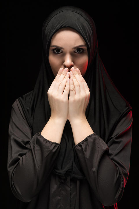 Portrait of beautiful serious young muslim woman wearing black hijab with hands Photo