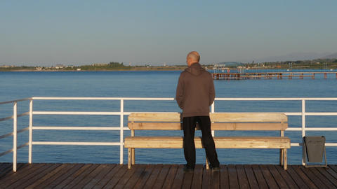Man walking on sea pier. Portrait adult man standing on sea pier Live Action