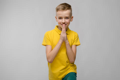 Portrait of cute little blonde caucasian boy in yellow t-shirt hoping on gray Photo