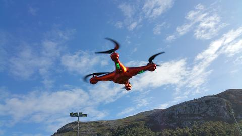 Orange quadcopter in the blue cloudy sky background Photo