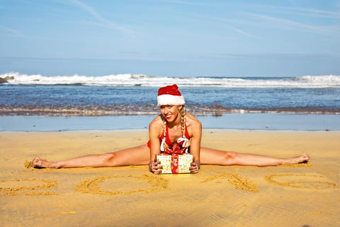 Young woman in santa hat with Christmas gift on twine in the beach フォト