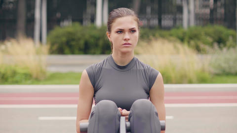 Young woman doing fitness exercise on workout ground in summer park Footage