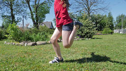 Girl is jumping on a jumping rope. Close up shot on legs. Slow motion Footage