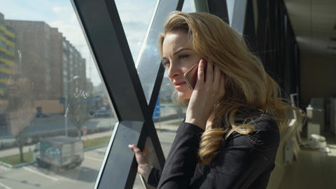 Beautisul blonde girl in black walking by the window and talking on the phone Photo