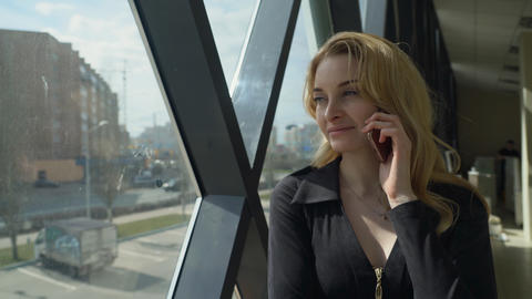 Beautisul blonde girl in black standing by the window and talking on the phone Photo