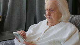 Old, senior woman is using smart phone Live Action
