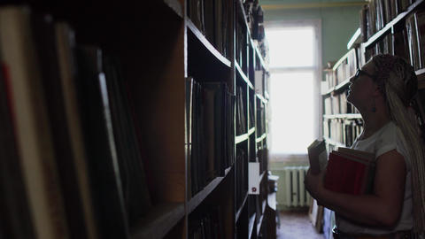 Beautiful blonde between the rows with books in the library Live Action