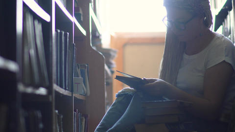Young girl is sitting on the floor between rows of books Footage