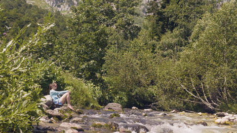 Rapid river flowing in mountain forest. Tourist woman resting on river shore Footage