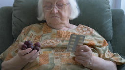 Funny old woman is throwing away medicine and is choosing sweet cherries Live Action