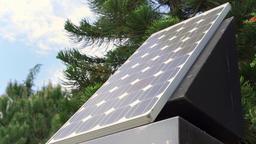 Solar panel agaist blue cloudy sky and green trees. New alternative energy Footage