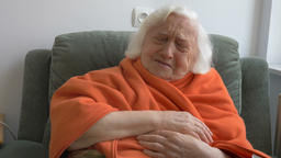 An old woman covered in orange blanket is laughing Footage