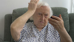 The old lady corrects the hairstyle and looks in the mirror Footage