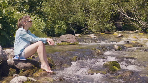 Tourist woman sitting on shore of stony river and resting while summer hike Footage