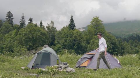 Tourist people eating and drinking while summer camping in mountain landscape Live Action