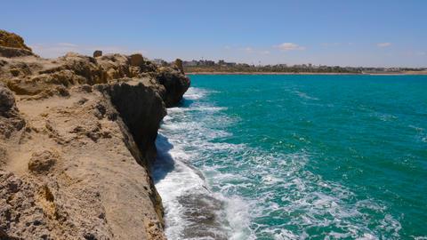 Scenic view sea waves on stony cliff on background Monastir city, Tunisia Live Action