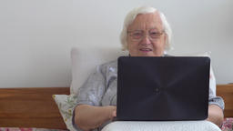 Funny old woman is browsing web pages on a laptop computer in a bed Footage