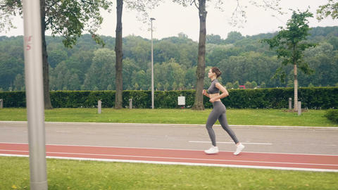 Young woman runner training in summer park. Sport and fitness training Live Action