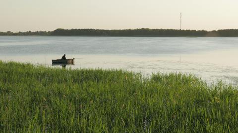 Fisherman in a boat fishing on a lake GIF