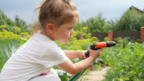 Happy Cute Girl Pours Water from a Hose on Vegetables in Summer Garden. 4K Footage