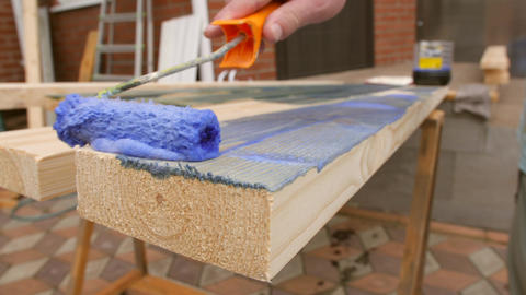 Carpenter Painting a Terrace Wooden Board with Impregnation Water Proofing or Live Action