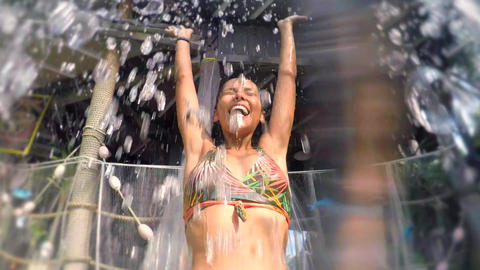 Young Mixed Race Girl Having Fun in Water Park. Waterfall Splash on Female Head Live Action