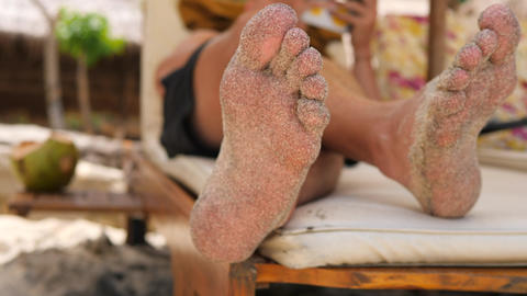 Sandy Male Feet on Lounge Bed at the Beach. 4K, Slowmotion. Bali, Indonesia Footage