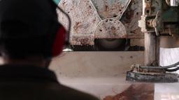 worker watching industrial saw sawing huge block of marble stone Footage