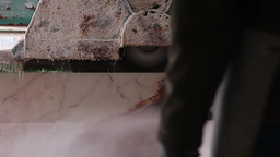 Man waiting for stone marble being cut by industrial saw, slider shot Footage