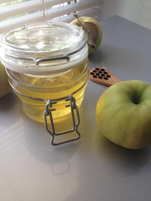 a honey jar and an apple on a light background フォト