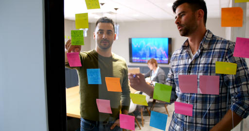 Executives working on sticky note on glass wall 4k Footage