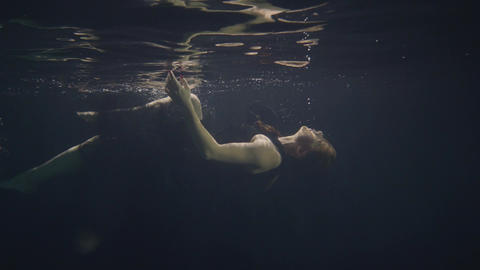 Fashion model in black dress swimming underwater on dark background Footage