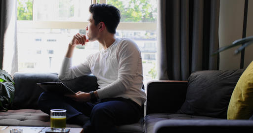 Man holding digital tab in looking out from window 4k Live Action