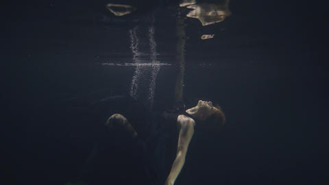 Young woman in black dress swimming underwater in pool while video shooting Footage