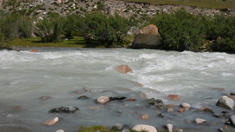 Flowing stony river in mountain valley. Rapid mountain river slow motion Footage