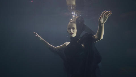 Young woman in black dress swimming underwater on dark background Footage