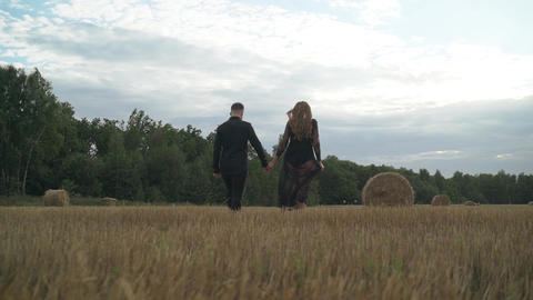 Awsome happy couple have fun in a field sunset background. Handsome Caucasian Footage