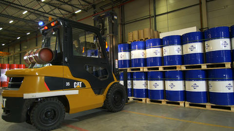 forklift takes and transports pallets with logo barrels from workers Live Action