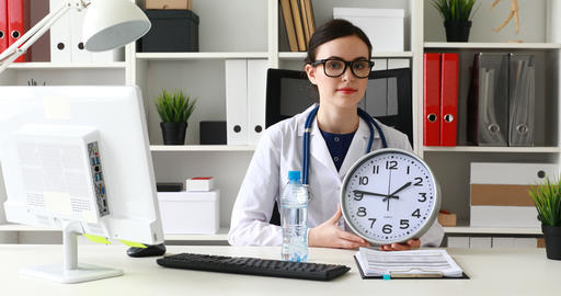 doctor holding clock in hand and holding out bottle of water at camera Live Action